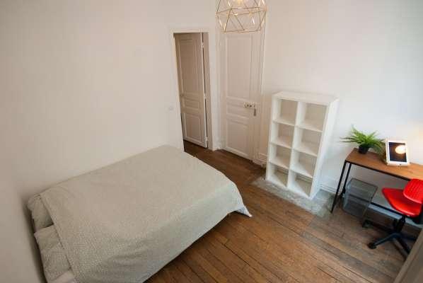 Belle chambre dans un immeuble Haussmanien avec parquet moulures et cheminées